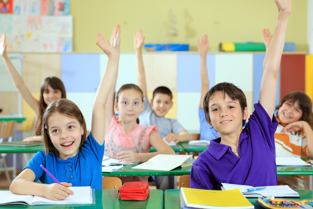 Slike za danas - Page 7 Elementary-school-students-raising-hands-in-classroom.