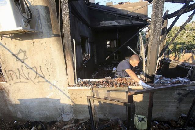 Palestina: Violencia ejercida por Israel en la ocupación. Respuestas y acciones militares palestinas. - Página 10 Agente-inspecciona-casa-quemada-cuya-pared-los-atacantes-pintaron-mensaje-hebreo-este-viernes-1438324478134
