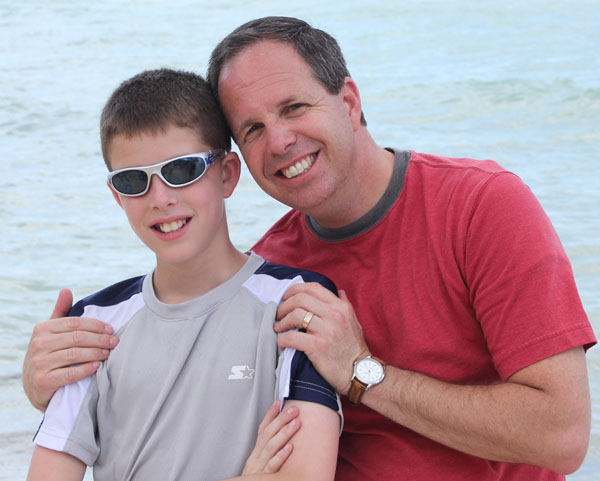 Fantasy Fanatics Podcast #1 Dad-teen-son-side-hug-on-water