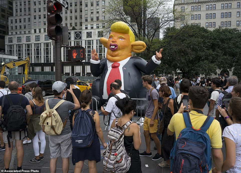 The Serious Side - part 3 - Page 17 1137091-4790620-An_inflatable_caricature_of_President_Donald_Trump_rises_above_p-a-2_1502753670680