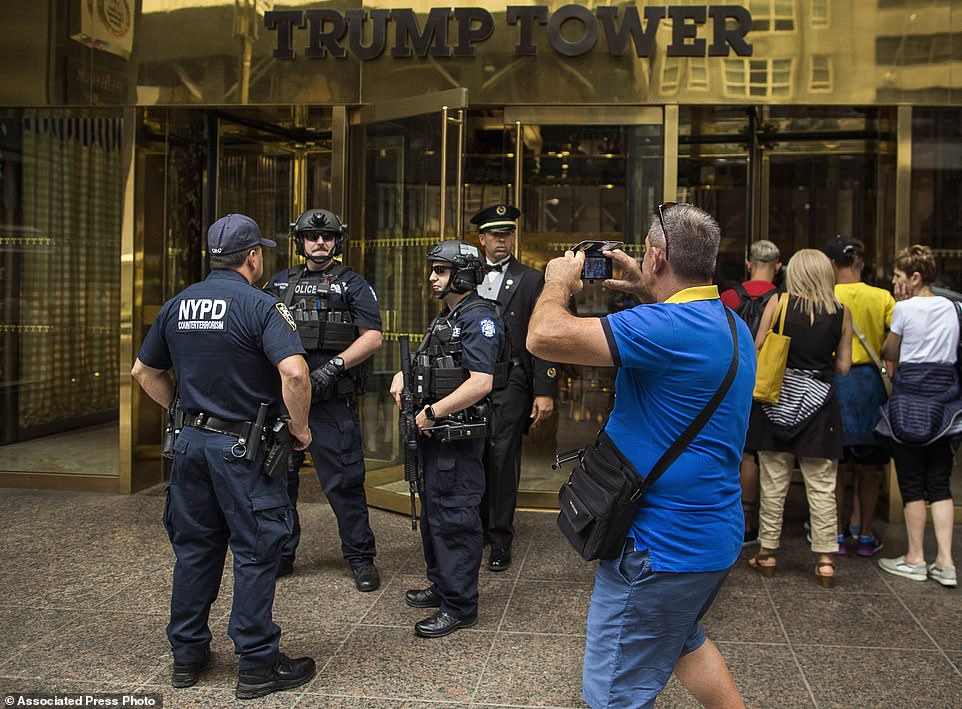 The Serious Side - part 3 - Page 17 1137105-4790620-Police_stands_guard_as_a_man_takes_pictures_in_front_of_Trump_To-a-9_1502753670796