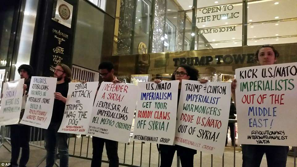 The Serious Side - part 6 - Page 3 4B23C56600000578-5614593-Protesters_stand_outside_Trump_Tower_demonstrating_against_milit-a-18_1523686646430