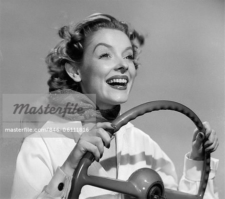 Det er fredag... - Page 2 846-06111816em-1950s-SMILING-WOMAN-WITH-HANDS-ON-STEERING-WHEEL-WITH-WIND-BLOWING-BAC