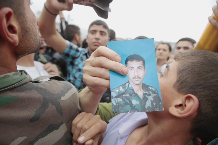 Le combat désespéré des familles de disparus syriens Syrien-village-dAzzara-province-Homs-brandit-portrait-proche-disparu-2012_0_729_486