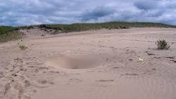 De mystérieux trous apparaissent à la surface d'une dune de sable Un-des-trous-forme-a-la-surface-de-la-dune_65525_w250