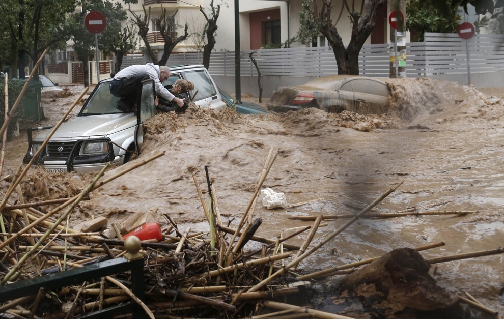 Картины и картинки - Страница 9 A-man-rescues-a-woman-from-her-car-on-a-flooded-road-in-the-athens-suburb-of-chalandri-in-february1