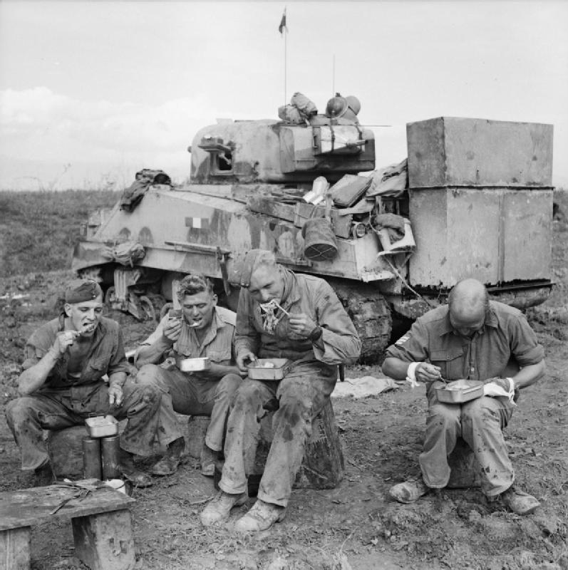 """Les ''Bricolages du bled"""" sur les shermans The-crew-of-a-Sherman-tank-fitted-with-deep-wading-equipment-enjoy-an-evening-meal-beside-their-vehicle-15-October-1943."""