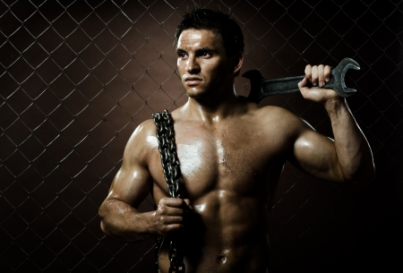 Cercasi... 14882182-il-muscoloso-lavoratore-uomo-bellezza-con-una-chiave-grande-e-catena-in-mano-su-rete-sfondo-recinzio