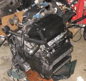 A frame, 2 engines, 8 brake callipers and 4 boxes of unknown parts K75f_021