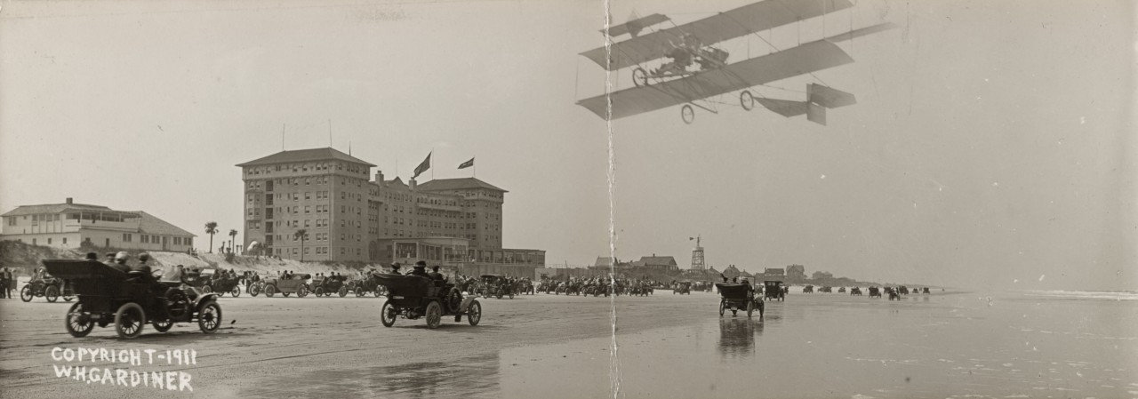 Des photos panoramiques anciennes de véhicules (Reportage photo) By Laboiteverte 13-Cars-on-beach-with-airplane-overhead-and-Clarendon-Hotel-in-background-Seabreeze-Daytona-Beach-Flor-1280x449