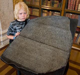 La pierre de Rosette: clé de compréhension de l'ancienne Egypte Bas-poses-reluctantly-next-to-a-replica-of-the-famed-rosetta-stone-at-the-british-museum