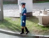 A smiling Pyongyang Traffic Woman about to step off the curb and do her favorite activity - directing traffic